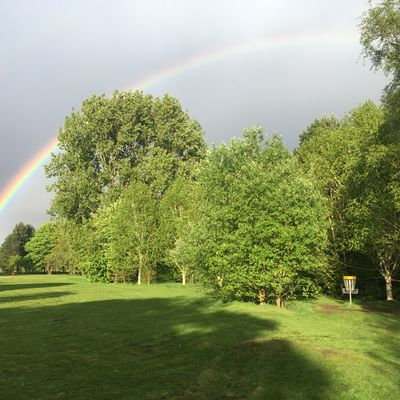 Looking back down the lush 18th fairway underneath a rainbow in springtime.